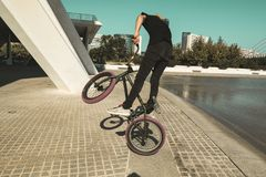 Guy with a bmx doing tricks for the city. Concept of young people doing extreme sports. BMX bike royalty free stock image