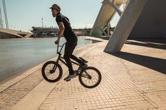 Guy with a bmx doing tricks for the city. Concept of young people doing extreme sports. Man with a bmx down the street stock photos