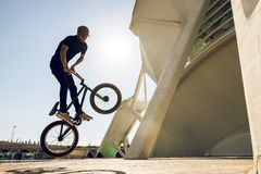 Guy with a bmx doing tricks for the city. Concept of young people doing extreme sports stock photo
