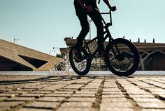 Guy with a bmx doing tricks for the city. Concept of young people doing extreme sports royalty free stock images