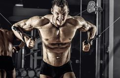 Guy bodybuilder with barbell. Guy bodybuilder, perform exercise with exercise machine crossover, in gym royalty free stock photo