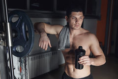 Guy bodybuilder tired in gym hold shaker with sportive nutrition Royalty Free Stock Photo