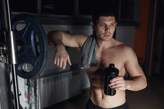 Guy bodybuilder tired in gym hold shaker with sportive nutrition - protein of shaker. Stock Photography