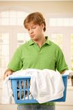 Guy bored of housework. Young guy bored of housework holding a basket of clothes to do washing Royalty Free Stock Photo