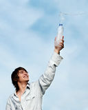 Guy with a bottle of water against sky Royalty Free Stock Photography