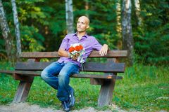 Guy with bouquet waiting for his girlfriend outsid Royalty Free Stock Photos