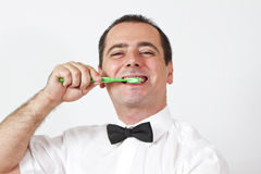 Guy with bow tie is brushing teeth Stock Images