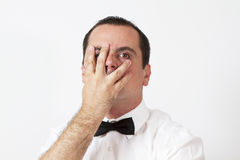 Guy with bow tie is holding hand on his face Stock Photos