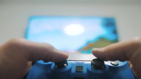 The guy boy is playing on controller joystick gamepad the console. Playing video games. online games internet on gamepad. The guy boy is playing on controller stock footage