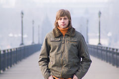 Guy on the bridge. Guy with long hair in khaki jacket is standing on the bridge looking straight into the camera Stock Images