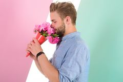Guy bring romantic pleasant gift waiting for her. Man ready for date bring pink flowers. Boyfriend confident holds stock images