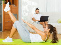 Guy browsing web while girl doing exercices Royalty Free Stock Photos