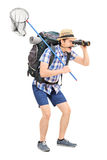 Guy with butterfly net looking through binoculars Stock Photos