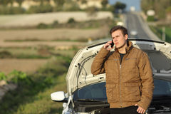 Guy calling roadside assistance for his breakdown car. I a country road stock images