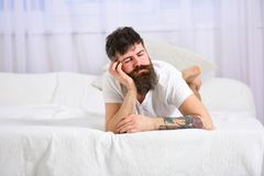 Guy on calm face sleeping on edge of bed. Exhausted concept. Man laying on bed, falling asleep while lean on hand, white. Guy on calm face sleeping on edge of stock images