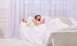 Guy on calm face sleeping on white sheets, pillow. Nap and siesta concept. Man laying on bed, covered with blanket royalty free stock image