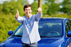 Guy with car key shows thumb up. Young happy man in glasses standing in front of his new car and showing thumb up and car key Royalty Free Stock Photos