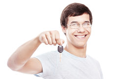 Guy with car keys. Portrait of young hispanic man wearing glasses and blue t-shirt holding out car keys and smiling isolated on white background - new drivers Stock Photos