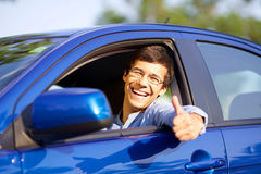 Guy in car with thumb up. Smiling handsome young driver showing thumb up through open car window Stock Photography