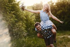 Guy carries his girlfriend on his back in summer outdoors royalty free stock photo
