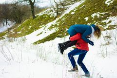 The guy carries his girlfriend on his shoulder in the winter meadow royalty free stock photo