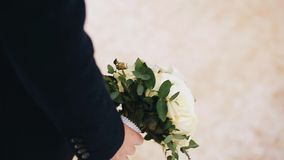 The guy carries in his hand a beautiful bouquet of flowers. Close up. The camera is in motion. Wonderful cinematic shots stock video footage