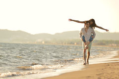 A guy carrying a girl on his back, at the beach, outdoors.  Royalty Free Stock Photo