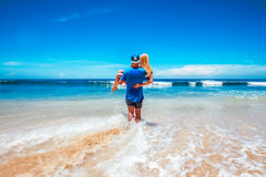 The guy is carrying his girlfriend to the ocean Royalty Free Stock Photos