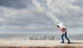 Guy carrying light bulb Stock Images