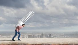 Guy carrying light bulb Stock Photography