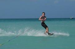Guy Carving joven en un Wakeboard en Aruba Foto de archivo