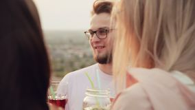 A guy of Caucasian appearance with a beard, glasses, standing on the Rooftop with his friends, drinking delicious. Cocktails and talking. summer urban cocktail stock footage