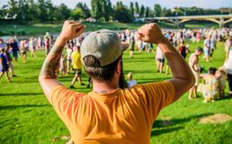Guy celebrate holiday or festival. Summer fest. Man bearded hipster in front of crowd. Open air concert. Book ticket now. Early bird sale. Music festival royalty free stock images