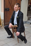 The guy on a chair. The young guy sits on a chair and smiles Royalty Free Stock Photo