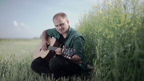 Guy in a checkered shirt plays on a guitar sitting in a summer field stock footage