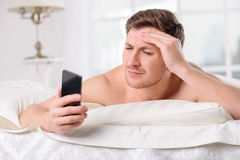Guy checks his social networks after awakening Royalty Free Stock Image