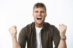 Guy cheering with excitement and joy yelling at camera supportive words clenching fists in joy and, being assertive. Boosting confidence, encourage friend to stock photo