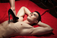 Guy on the chest is female foot in shoe heel. Royalty Free Stock Photo