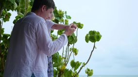 Guy and child on the terrace, looking out to sea.Panoramic view stock footage