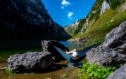 Guy chilling in a hammock between two stones at a mountain lake enjoing the view stock image