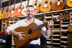 Guy choosing guitar in music shop Royalty Free Stock Images