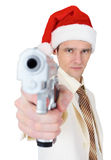 Guy in Christmas hat aiming a gun Royalty Free Stock Image