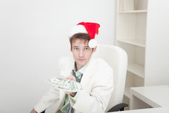 Guy in Christmas hat gives us money Royalty Free Stock Photo