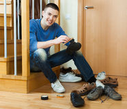 Guy cleaning footwear Stock Image