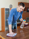 Guy cleaning furniture with cleanser and rag at living room. Smiling guy cleaning furniture with cleanser and rag at living room Royalty Free Stock Image