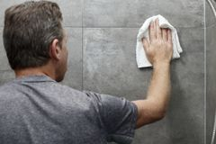 Guy Cleaning Gray Tile Bathroom Shower Wall con un trapo imagen de archivo