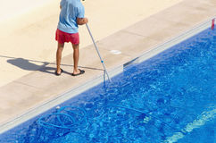 Guy cleaning the swimming pool with a brush Stock Image