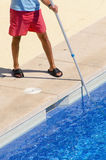 Guy cleaning the swimming pool with a brush Royalty Free Stock Photography