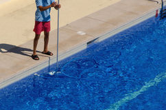 Guy cleaning the swimming pool with a brush Royalty Free Stock Photos