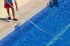 Guy cleaning the swimming pool with a brush from the poolside Royalty Free Stock Images